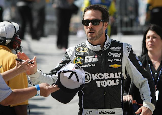 Jimmie Johnson gives a high-five to a fan as he arrives on pit road before the NASCAR Sprint Cup auto race in Dover, Del., Sunday, Sept. 29, 2013. Johnson won the race. (AP Photo/The News-Journal, Suchat Pederson)