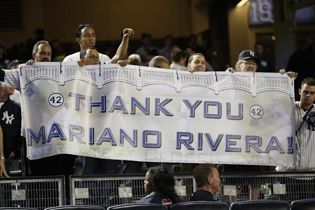 Fans hold a sign for New York Yankees relief pitcher Mariano Rivera (42) who pitched in his final appearance at a baseball game at Yankee Stadium, Thursday, Sept. 26, 2013, in New York. (AP Photo/Kathy Willens)