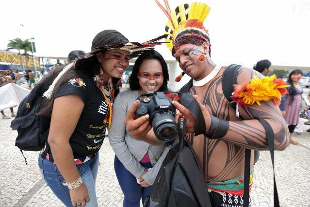 Indigenous people of different ethnic groups look at a photograph on a camera during a protest against the Indian policy of President Dilma Rousseff's government and the costs of the 2014 World Cup in front of the Planalto Palace in Brasilia May 27, 2014. REUTERS/Joedson Alves (BRAZIL - Tags: SOCIETY SPORT SOCCER WORLD CUP POLITICS CIVIL UNREST)