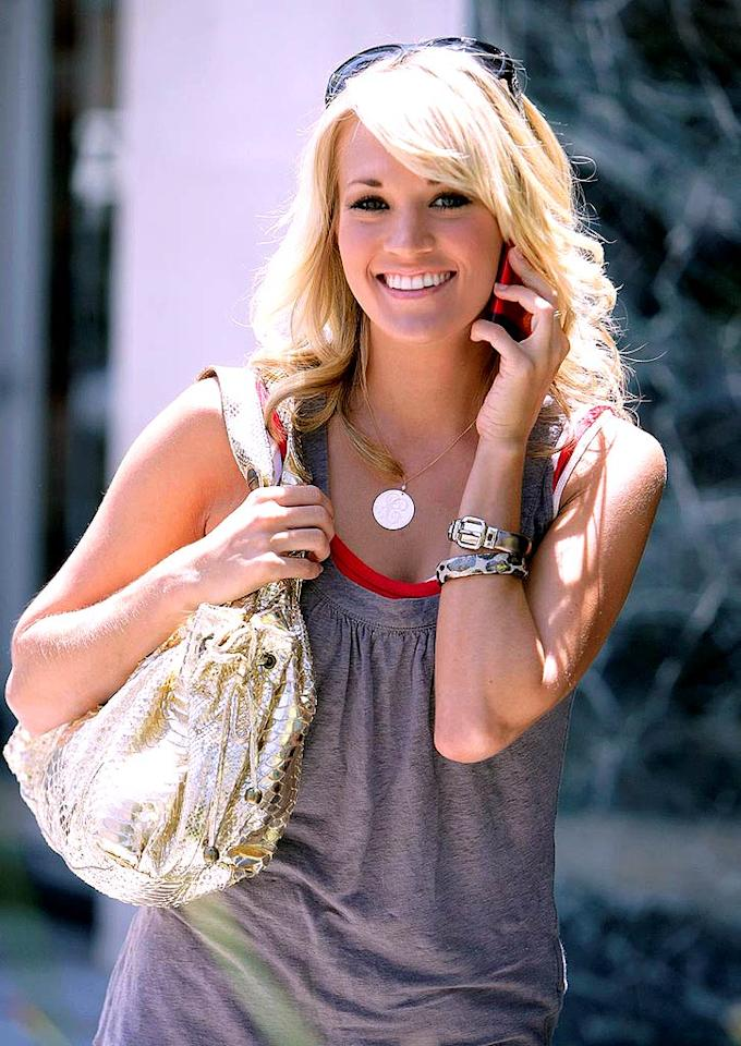 "Gold accessories are all the rage this summer, and Carrie Underwood's mammoth metallic handbag is undeniably hot. Anthony Visschedyk/<a href=""http://www.pacificcoastnews.com/"" target=""new"">PacificCoastNews.com</a> - July 24, 2008"