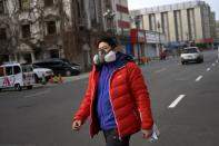 Man wearing a protective face mask walks on a street, as the country is hit by an outbreak of the novel coronavirus, in Beijing