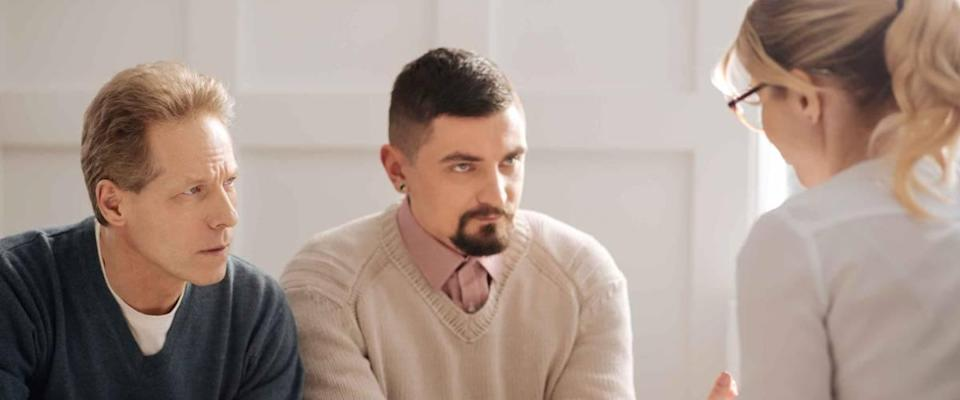 Serious anxious gay couple listening to financial adviser.