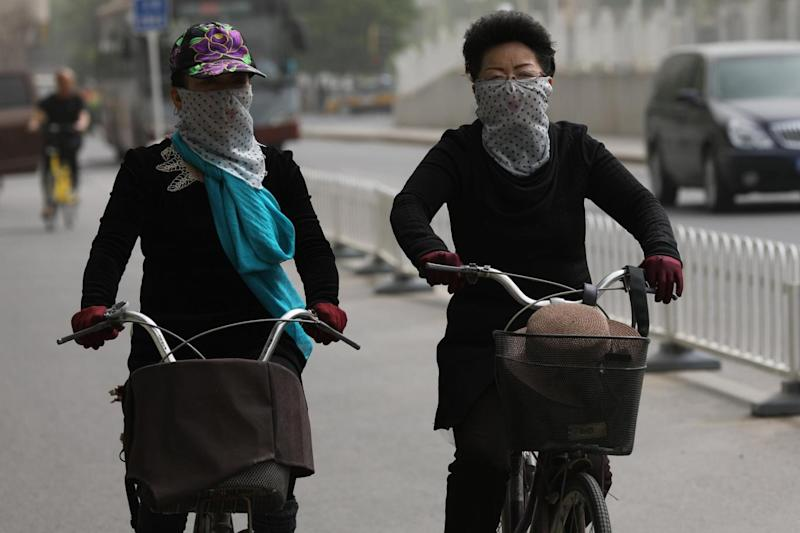 Cyclists in Beijing protect their noses and mouths (EPA)