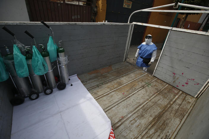 City worker Carlos Ruiz loads tanks of oxygen for COVID-19 patients, in the Iztapalapa borough of Mexico City, Friday, Jan. 15, 2021. The city offers free oxygen refills for COVID-19 patients. (AP Photo/Marco Ugarte)
