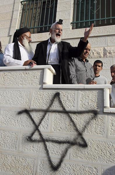 FILE- In this Sept. 6, 2011, file photo, Jewish rabbi Menachem Froman, center, leads a reconciliation visit of Jewish settlers to the West Bank village of Qusra, a day after the local mosque was vandalized. Rabbi Menachem Froman, an Israeli settler known for his efforts to promote coexistence between Arabs and Jews, died Monday Feb. 4, 2013, after a long illness. He was 68. (AP Photo/Nasser Ishtayeh, File)