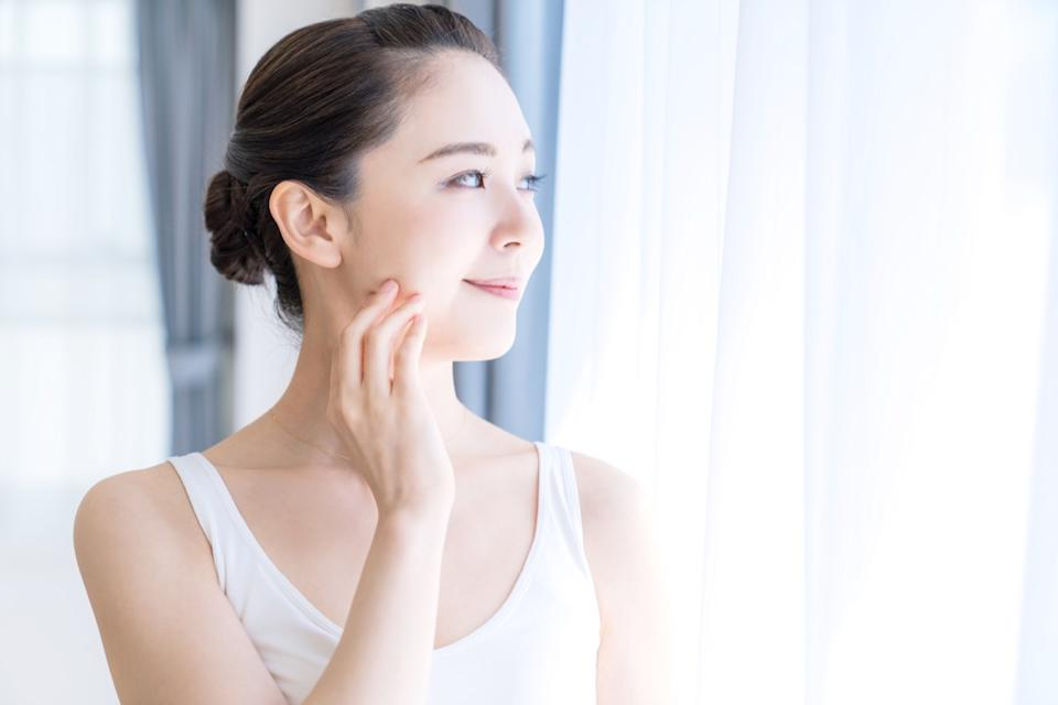 woman touching her face while staring out the window