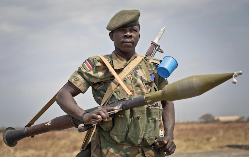 A South Sudanese government soldier stands guard as a delegation of visiting officials leaves from the airport in Malakal, Upper Nile State, in South Sudan Tuesday, Jan. 21, 2014. The government said Monday that it had regained control of Malakal, the capital of the oil-producing Upper Nile state, though the U.N. said its base there took fire, wounding nearly three dozen people and damaging the hospital. (AP Photo/Mackenzie Knowles-Coursin)