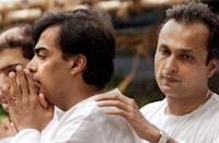 Mukesh Ambani (L) is comforted by his younger brother Anil Ambani (R) on the funeral cortege carrying the body of their father Dhirubhai Ambani, founder and chairman of India's largest private sector company Reliance Industries, to the Chandanwadi crematorium in Bombay, 07 July 2002. Ambani died late 06 July at the the Breach Candy hospital where he was adimitted 24 June after he suffered a stroke. AFP PHOTO / Sebastian D'SOUZA.