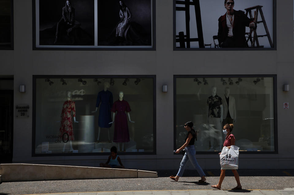 A woman, right, wearing a face mask, walks outside of a shop at Makarios main shopping street in capital Nicosia, Cyprus, Friday, July 31, 2020. Cyprus has made mask-wearing compulsory in all indoor areas where people gather in large numbers like malls and supermarkets and is significantly ramping up random coronavirus testing at it's two main airports following an upsurge of new confirmed cases in the last week that has alarmed authorities. (AP Photo/Petros Karadjias)
