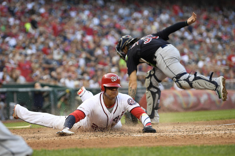 Washington Nationals' Juan Soto, left, slides home to score against Cleveland Indians catcher Eric Haase, back, during the fourth inning of a baseball game, Saturday, Sept. 28, 2019, in Washington. (AP Photo/Nick Wass)