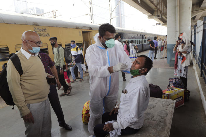 A health worker takes a swab sample of a commuter to test for COVID-19 at a train station in Mumbai, India, Thursday, Feb. 11, 2021. When the coronavirus pandemic took hold in India, there were fears it would sink the fragile health system of the world's second-most populous country. Infections climbed dramatically for months and at one point India looked like it might overtake the United States as the country with the highest case toll. But infections began to plummet in September, and experts aren't sure why. (AP Photo/Rajanish Kakade)