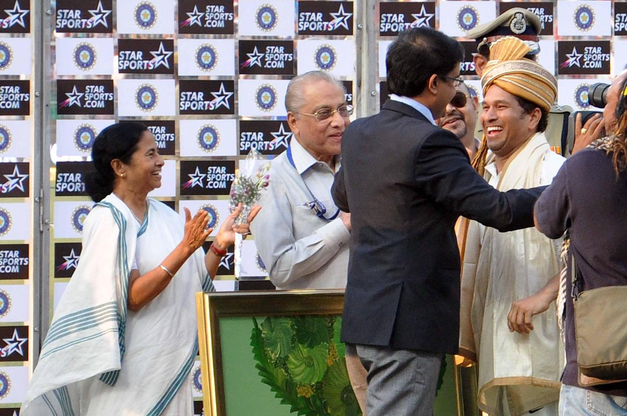 West Bengal Chief Minister Mamata Banerjee and former BCCI President Jagmohan Dalmiya clap as former cricketer Sourav Ganguly hugs master blaster Sachin Tendulkar as India won 1st test match between India and West Indies at Eden Gardens, Kolkata on Nov. 8, 2013. (Photo: IANS)