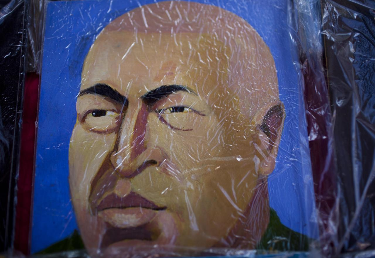 A painting wrapped in plastic of Venezuela's President Hugo Chavez is displayed on an easel on a street in Caracas, Venezuela, Friday March 2, 2012. Chavez has been in Cuba since last Friday to have a growth removed in the same part of the pelvis where a larger, malignant tumor was extracted last year. Chavez said Friday he's recovering quickly from tumor surgery, that doctors have put him on a special diet, and that he's taking daily walks. (AP Photo/Ariana Cubillos)