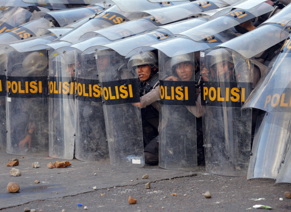 Riot police officers take defensive position during a clash with student protesters in Jakarta, Indonesia, Monday, Sept. 30, 2019. Thousands of Indonesian students resumed protests on Monday against a new law they say has crippled the country's anti-corruption agency, with some clashing with police. (AP Photo/Tatan Syuflana)