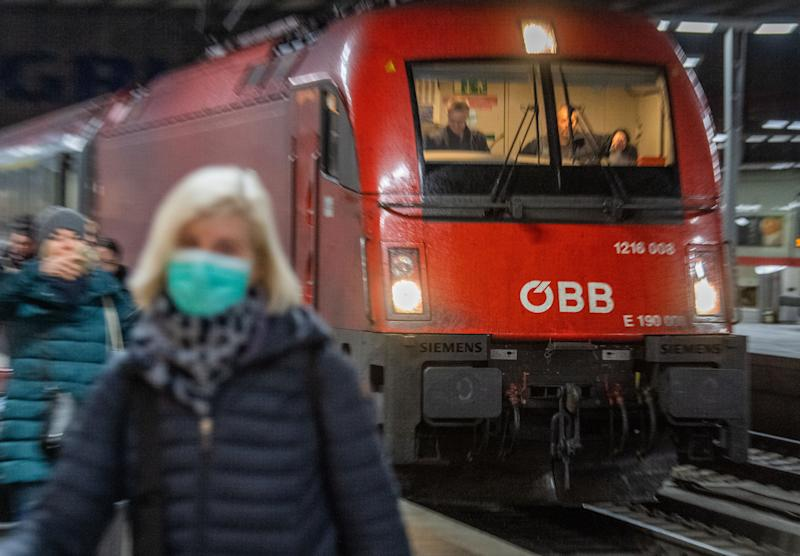 24 February 2020, Bavaria, Munich: A woman wearing a breathing mask walks in front of the Eurocity train along the main station in Munich. The train, stopped at the Brenner Pass for fear of the corona virus, arrived in Munich early Monday morning, several hours late. Photo: Lino Mirgeler/dpa (Photo by Lino Mirgeler/picture alliance via Getty Images)