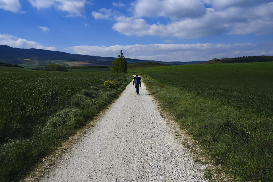 """Martim Thomas, 41, from Switzerland, walks along a path during a stage of """"Camino de Santiago"""" or St. James Way near Pamplona, northern Spain, Thursday, April 14, 2021. The pilgrims are trickling back to Spain's St. James Way after a year of being kept off the trail due to the pandemic. Many have committed to putting their lives on hold for days or weeks to walk to the medieval cathedral in Santiago de Compostela in hopes of healing wounds caused by the coronavirus. (AP Photo/Alvaro Barrientos)"""