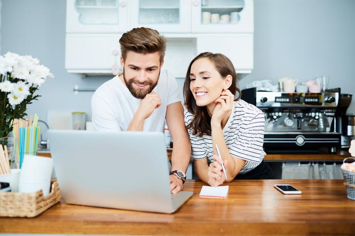 Young man and woman, behind the counter of what looks like an eatery or coffee shop, looking at a laptop screen.