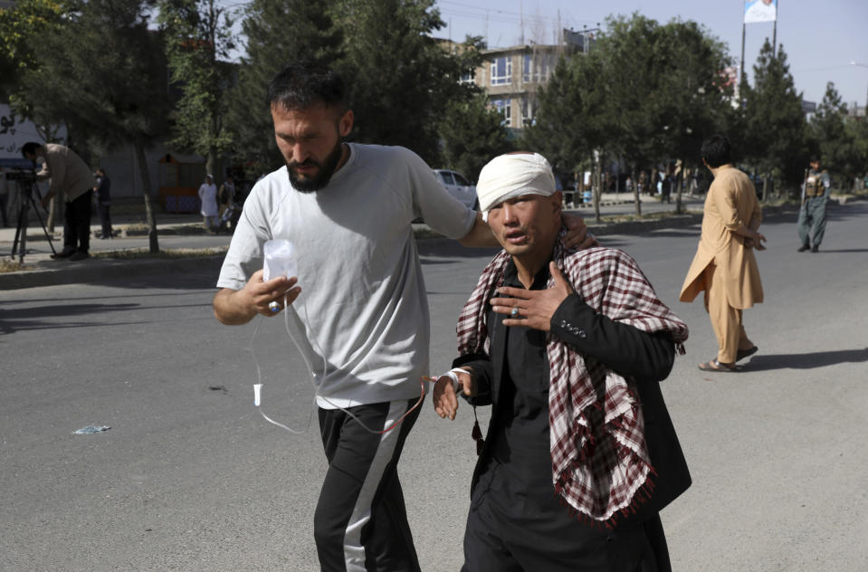 An Afghan man helps an injured man after a bomb explosion in Kabul, Afghanistan, Saturday, June 12, 2021. Separate bombs hit two minivans in a mostly Shiite neighborhood in the Afghan capital Saturday, killing several people and wounding others, the Interior Ministry said. (AP Photo/Rahmat Gul)