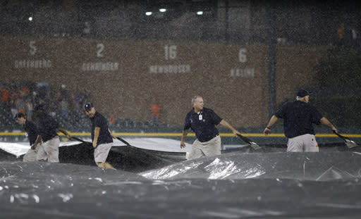 Comerica Park grounds crew members pulls the tarp across the field as rain falls during the seventh inning of a baseball game between the Detroit Tigers and Cleveland Indians, Friday, Aug. 30, 2013, in Detroit. (AP Photo/Duane Burleson)