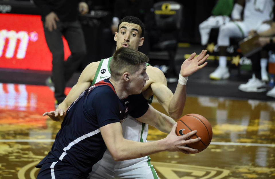 Arizona forward Azuolas Tubelis, front, is guarded by Oregon guard Chris Duarte (5) as he drives to the basket during the first half of an NCAA college basketball game Monday, March 1, 2021, in Eugene, Ore. (AP Photo/Andy Nelson)
