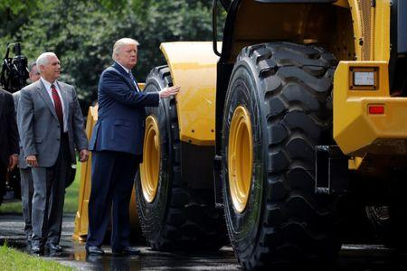 "U.S. President Donald Trump and Vice President Mike Pence stand next to caterpillar equipment as they visit a ""Made in America"" products showcase at the White House in Washington, U.S., July 17, 2017. REUTERS/Carlos Barria"