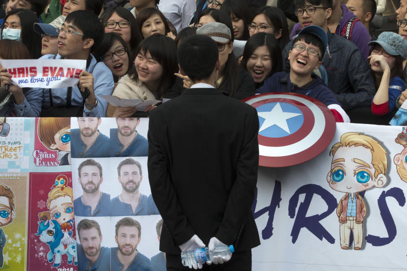"""In this Monday, March 24, 2014 photo, fans wait for the arrival of Chris Evans, the actor playing the lead role, during a publicity event ahead of the April release of his movie """"Captain America: The Winter Soldier"""" in Beijing. Captain America and Spiderman are seeking to dominate the Chinese box office in the coming weeks, proving that U.S. patriotic superheroes can overcome China's leeriness of foreign films if they promise big money. Chinese authorities, wary of outside cultural influences and competition, restrict the number of foreign movies shown in the mainland's cinemas to 34 each year. (AP Photo/Ng Han Guan)"""