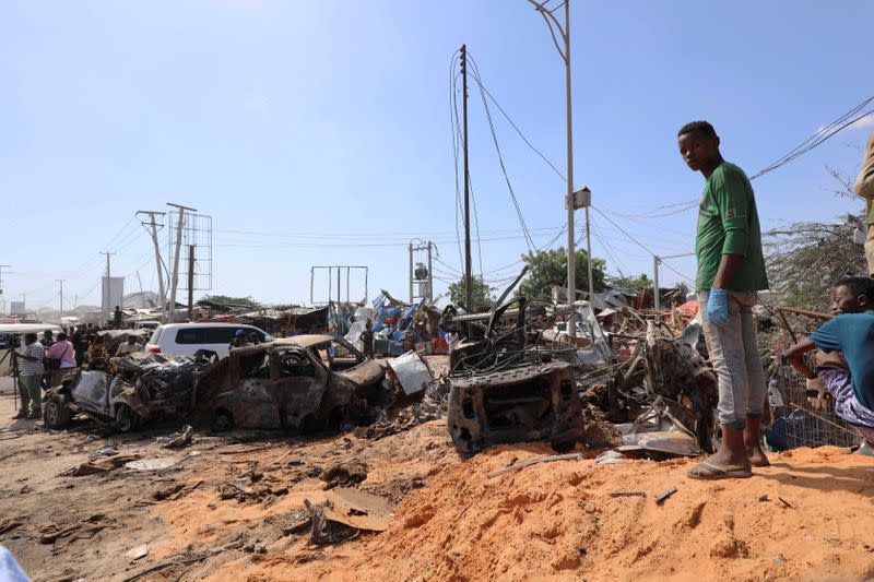 A Somali man stands at the scene of a car bomb explosion at a checkpoint in Mogadishu