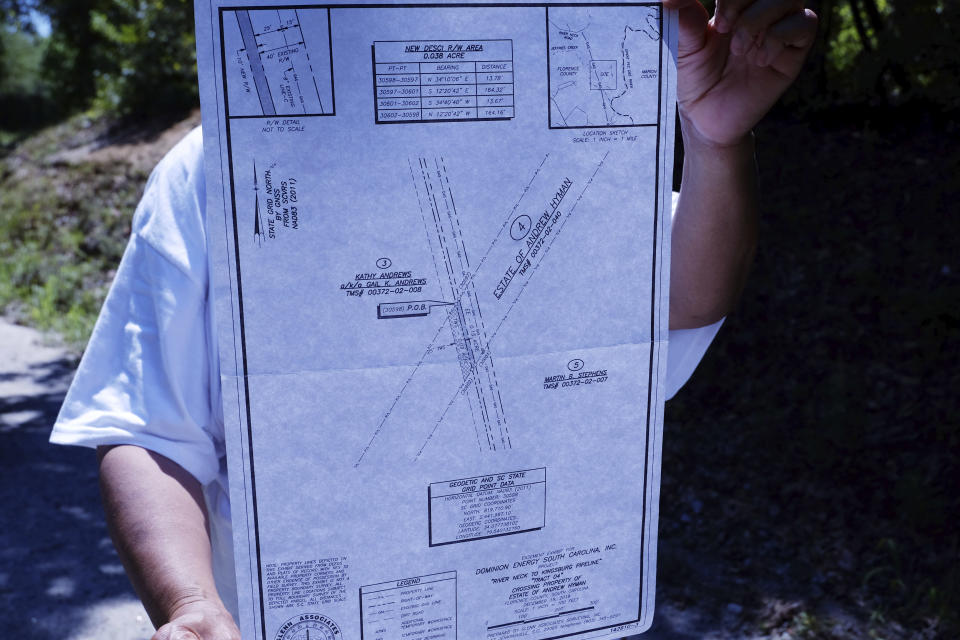 Reatha Jefferson holds documents showing where Dominion Energy has proposed a gas line to run through the land her family owns near Pamplico, S.C., on Monday, Aug. 17, 2020. Dominion Energy served Jefferson with court papers in July to initiate eminent domain proceedings to run a natural gas pipeline through the land Jefferson's family owns. (AP Photo/Michelle Liu)