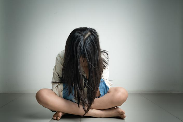 A girl sitting on the floor with her face covered. (PHOTO: Getty Images)