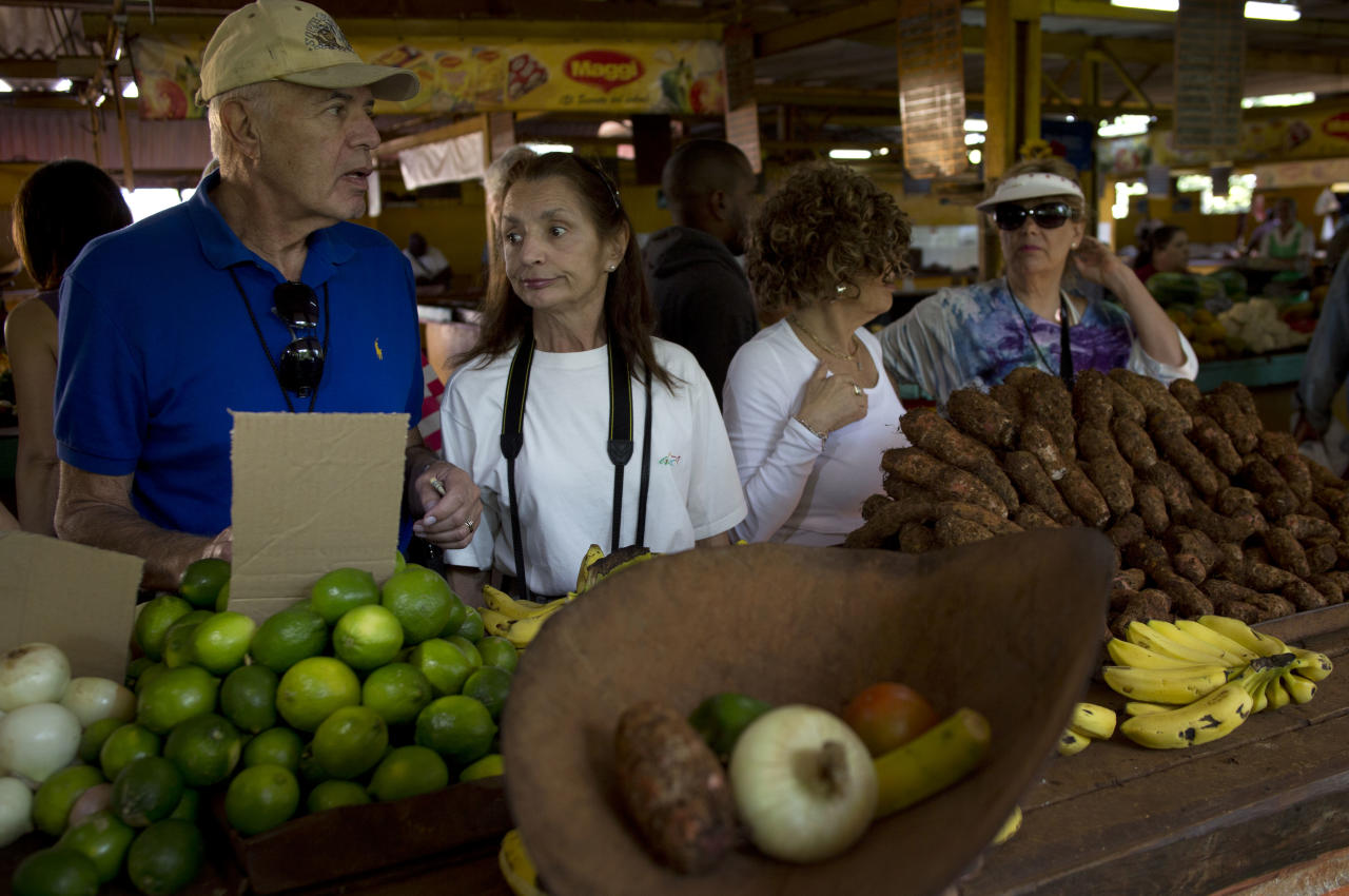"In this Jan. 23, 2014 photo, tourists traveling with the ""people-to-people"" program make a purchase in a Cuban agricultural market in Havana, Cuba. Tour operators insist they're supporting local organic farmers, performers, artists, musicians and entrepreneurs who run private restaurants, adding that the Cuban government's involvement in scheduling is minimal and agendas carefully comply with U.S. rules barring sun-and-sand tourism. (AP Photo/Ramon Espinosa)"