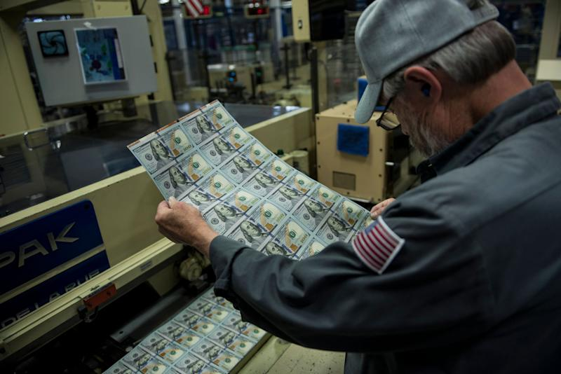 John Guy inspects a sheet of money during the phase of production where the new 100 USD bills are applied with a serial number, a US Federal Reserve seal, are cut and stacked at the US Bureau of Engraving and Printing's Western Currency Facility October 11, 2013 in Fort Worth, Texas. The facility is currently the sole producer of the new 100 USD bill. The bill went into circulation on October 8 and includes new security features such as a purple band with moving images, ink that changes color with the angle as well as a new more colorful design. AFP PHOTO/BRENDAN SMIALOWSKI (Photo credit should read BRENDAN SMIALOWSKI/AFP/Getty Images)