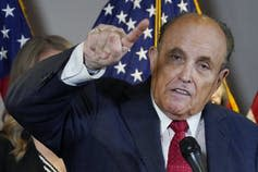 Rudy Giuliani gestures at a news conference.