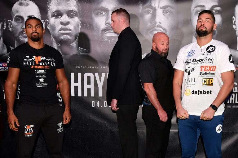 British boxers David Haye (L) and Tony Bellow (R) are seperated by security personel as they pose for photographers following a press conference
