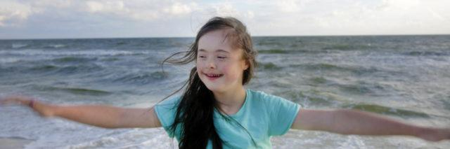 Girl with Down syndrome at the beach.