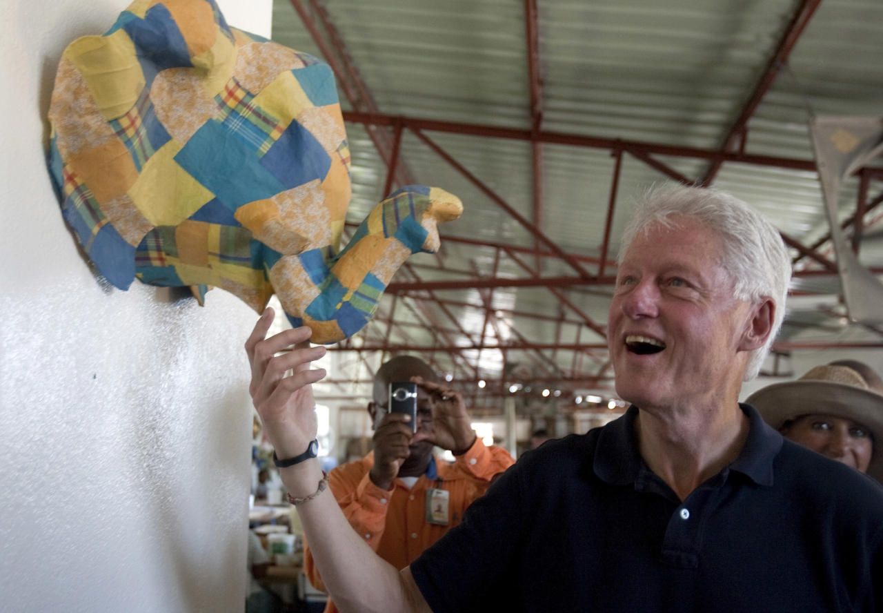 Former U.S. President and UN special envoy to Haiti, Bill Clinton reacts as he watches a craftwork during a visit to the Caribbean Craft art workshop in Port-au-Prince, Haiti, Tuesday, Aug. 16, 2011. (AP Photo/Dieu Nalio Chery)