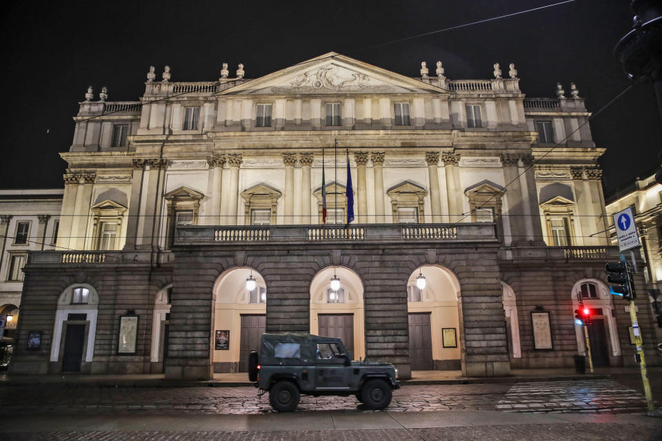 """FILE - In this early Sunday, Oct. 25, 2020 file photo, A military vehicle drives past La Scala opera theater in Milan, northern Italy. The number of performers at Milan's famed La Scala opera house positive with the coronavirus has risen to 21, even as the theater was forced to close due to new government restrictions aimed at curbing the virus' resurgence. La Scala spokesman Paolo Besana confirmed Tuesday that 18 members of the world-class chorus and three woodwind players in the orchestra have the virus. That comes after two singers, including tenor Francesco Meli, tested positive, ahead of planned concert performances last week of """"Aida.''(AP Photo/Luca Bruno, File)"""