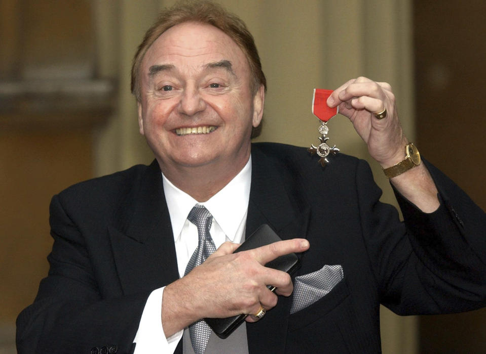 "FILE - In this Dec. 12, 2003 file photo, Gerry Marsden holds his MBE. Gerry Marsden, the British singer and lead singer of Gerry and the Pacemakers, who was instrumental in turning a song from the Rodgers and Hammerstein musical ""Carousel"" into one of the great anthems in the world of football, has died. He was 78. (Matthew Fearn/PA via AP, File)"