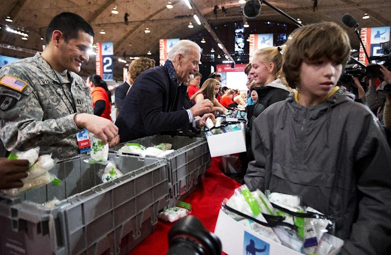 Vice President Joe Biden, center, fills care kits with necessities for deployed U.S. service members, wounded warriors, veterans and first responders, joining the National Day of Service as part of the 57th presidential inauguration in Washington, Saturday, Jan. 19, 2013. Volunteer Nathan Fouse walks with a care kit at right.    (AP Photo/Manuel Balce Ceneta)