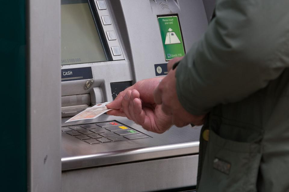 """File photo dated 14/09/17 of a man withdrawing money from an ATM. The coronavirus pandemic should give banks a """"kick up the bum"""" to invest in cutting-edge technology to ensure vital access to cash in a post-Covid-19 world, according to one of the world's largest cash machine makers."""