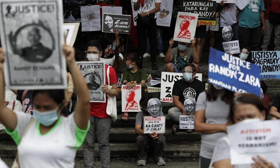 rotesters hold pictures of human rights activists killed in the Philippines