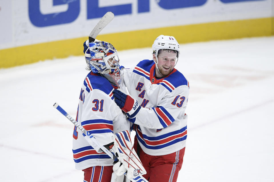 New York Rangers goaltender Igor Shesterkin (31) and left wing Alexis Lafrenière (13) celebrate after an NHL hockey game against the Washington Capitals, Saturday, Feb. 20, 2021, in Washington. The Rangers won 4-1. (AP Photo/Nick Wass)