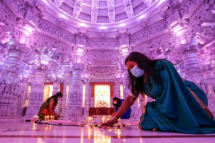 Women wearing masks and traditional robes kneel around a work of sand art inside an intricate Hindu temple