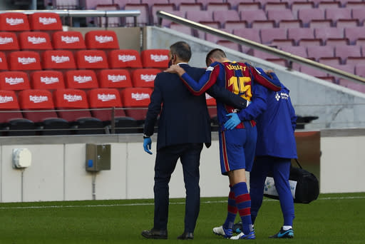 Barcelona's Clement Lenglet leaves the pitch injured during the Spanish La Liga soccer match between FC Barcelona and Osasuna at the Camp Nou stadium in Barcelona, Spain, Sunday, Nov. 29, 2020. (AP Photo/Joan Monfort)