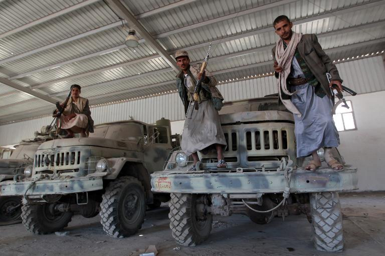 Yemeni Huthi rebels pose on military vehicles at an army base which they captured just hours before the signing a UN-brokered peace agreement on September 22, 2014 in Sanaa