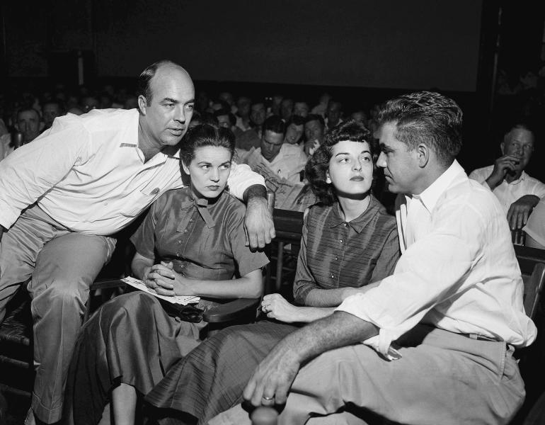 "FILE - In this Sept. 23, 1955, file photo, J.W. Milam, left, his wife, second left, Roy Bryant, far right, and his wife, Carolyn Bryant, sit together in a courtroom in Sumner, Miss. Bryant and his half-brother Milam were charged with murder but acquitted in the kidnap-torture slaying of 14-year-old black teen Emmett Till in 1955 after he allegedly whistled at Carolyn Bryant. The men later confessed in a magazine interview but weren't retried; both are now dead. Citing ""new information,"" the U.S. Justice Department has reopened the investigation into Till's death. (AP Photo, File)"