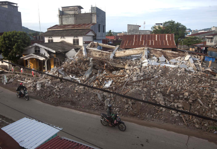 Motorists ride past buildings collapsed in Friday's earthquake in Mamuju, West Sulawesi, Indonesia, Monday, Jan. 18, 2021. Aid was reaching the thousands of people left homeless and struggling after an earthquake that killed a number of people in the province where rescuers intensified their work Monday to find those buried in the rubble. (AP Photo/Yusuf Wahil)
