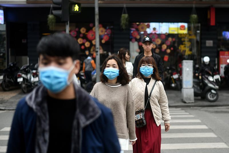 Pedestrians, wearing protective facemasks amid concerns of the novel coronavirus outbreak, cross a street in Hanoi on February 7, 2020. (Photo by Manan VATSYAYANA / AFP) (Photo by MANAN VATSYAYANA/AFP via Getty Images)