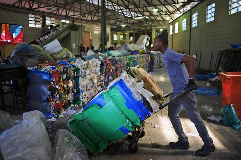 A men works in the recycling of plastic bags at CoopFuturo, a sorting collective which receives rubbish from the local government collection service and then sells the material to specialized recycling companies, in Rio de Janeiro, Brazil (AFP Photo/CARL DE SOUZA)