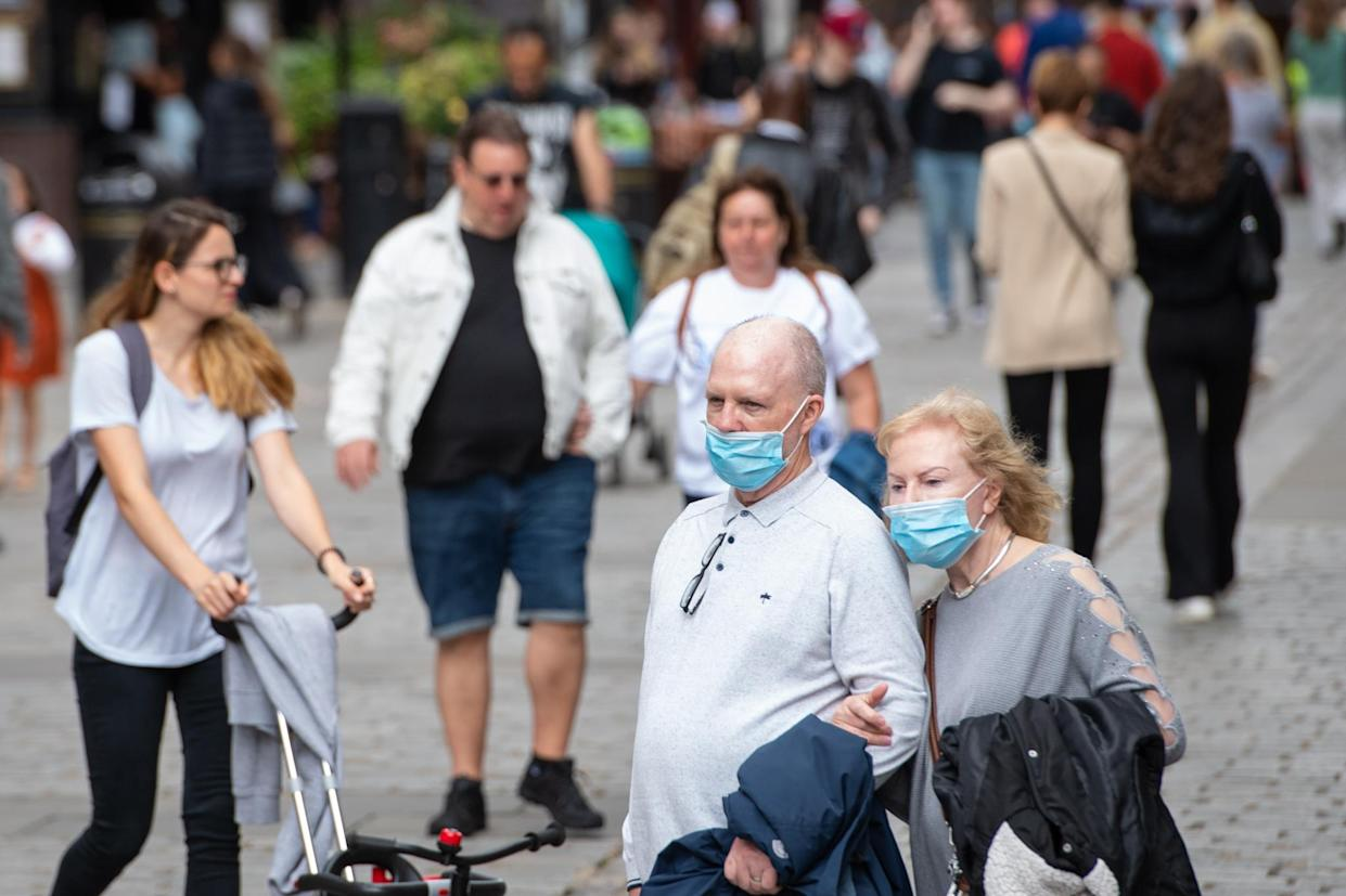 People wearing face masks watch a street entertainer in Covent Garden, London. Rumours were abound in the Sunday newspapers that Prime Minister Boris Johnson, who is due to update the nation this week on plans for unlocking, is due to scrap social distancing and mask-wearing requirements on so-called