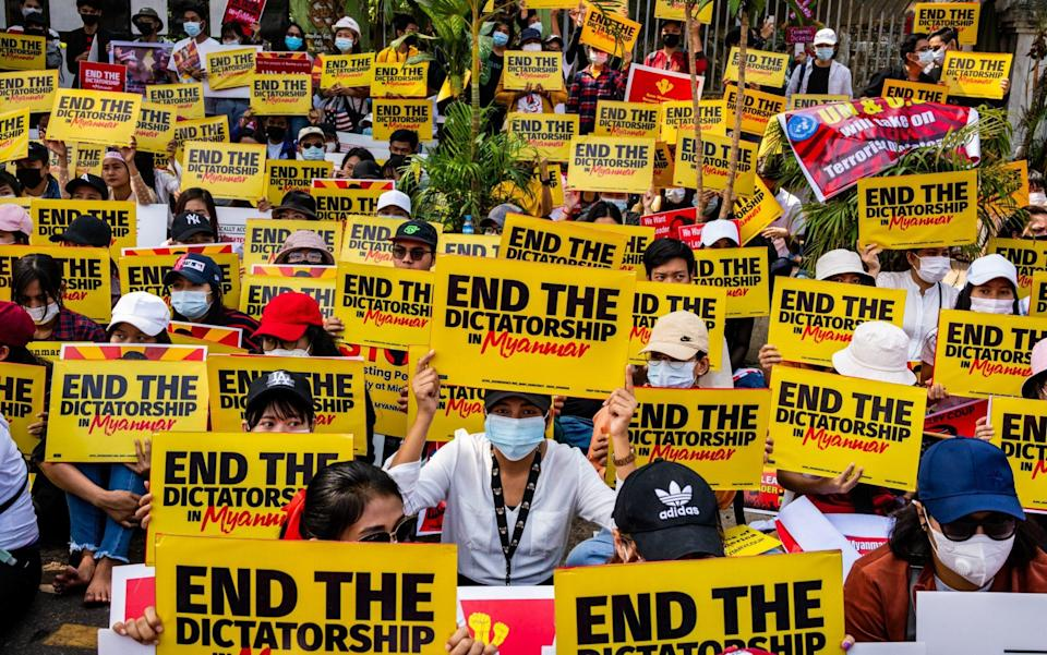 Myanmar protesters hold banners as they gather outside the US Embassy